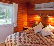 Main bedroom with kingsize bed, built-in wardrobes and forest views